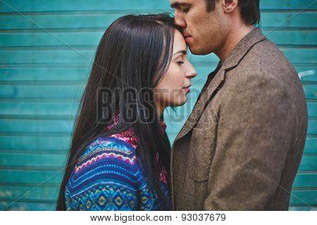 Amorous man kissing young woman on forehead
