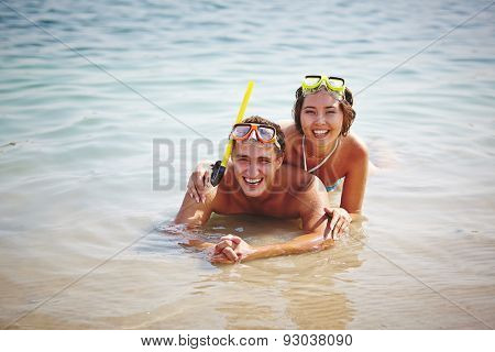Happy divers looking at camera in water