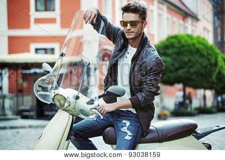Handsome man riding a vintage scooter
