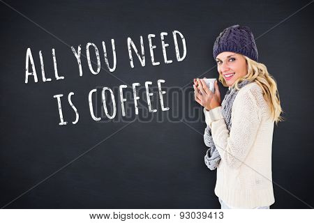 Pretty blonde in winter fashion holding mug against black background