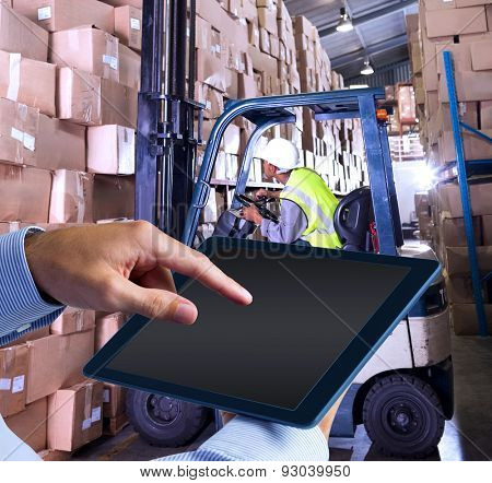 Man using tablet pc against forklift machine in warehouse