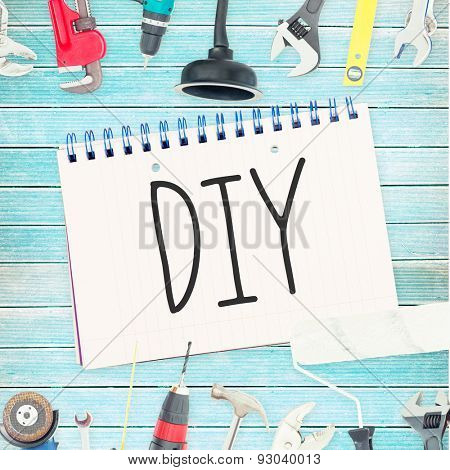 The word diy against tools and notepad on wooden background