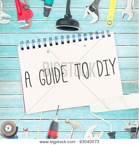 The word a guide to diy against tools and notepad on wooden background