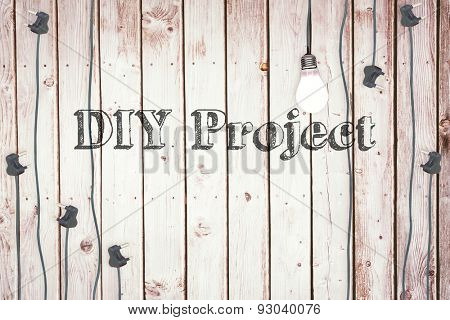The word diy project against light bulb on wooden background