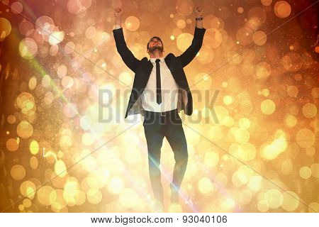 Cheerful businessman with arms up cheering against yellow abstract light spot design