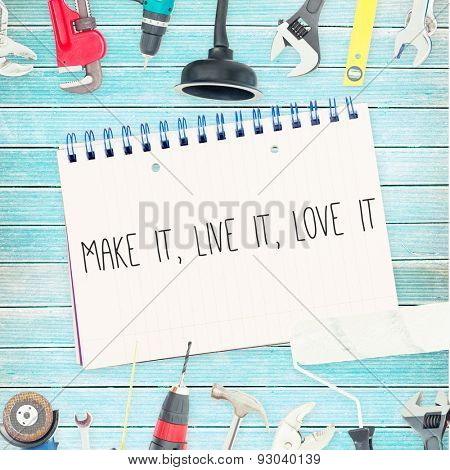 The word make it, live it, love it against tools and notepad on wooden background