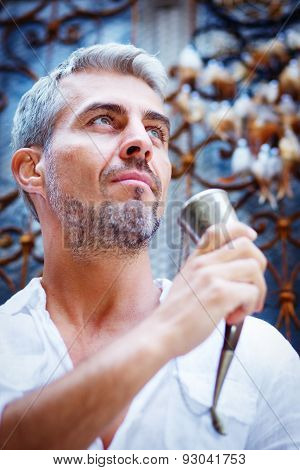 Sexi Man In A White Shirt And Medieval Mead Horn In Hand. Ornamental Window On Background, And Dream