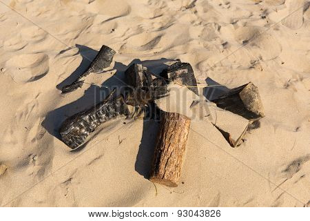 Remains of a small campfire with burned wood logs and sand on a beach