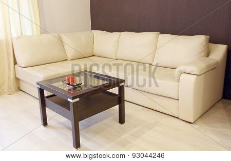 Modern White Corner Leather Sofa And Wooden Table.