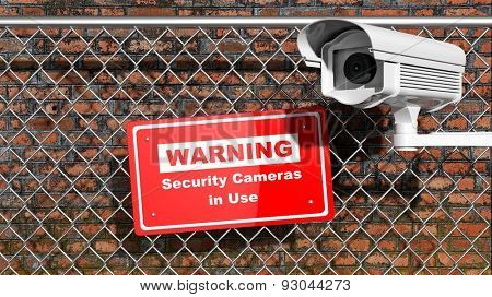 Security surveillance camera on chain-link fence with warning sign