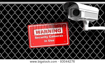 Security surveillance camera on chain-link fence with warning sign on black