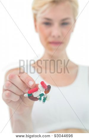 Blonde woman throwing away batch of pills on white background