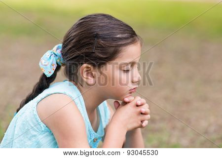 Little girl saying his prayers on a sunny day
