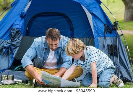 Father and son camping and looking for their way home on a sunny day