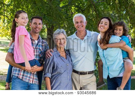 Extended family smiling at the camera on a sunny day