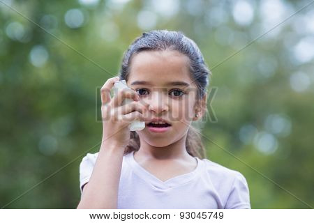 Little boy using his inhaler on a sunny day
