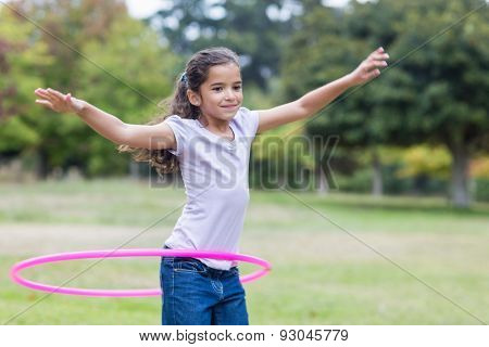 happy girl playing with hula hoops on a sunny day