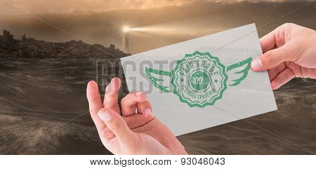 Hand showing card against stormy sea with lighthouse