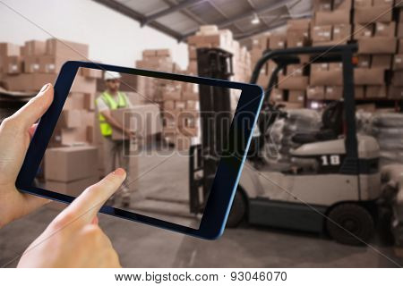 Man using tablet pc against warehouse worker loading up pallet