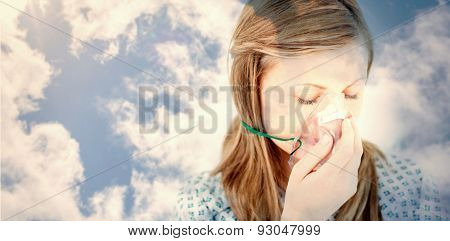 Bright blue sky with clouds against depressed female patient with a mask