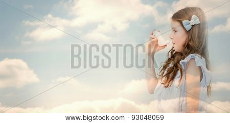 Cloudy sky against little girl taking inhaler