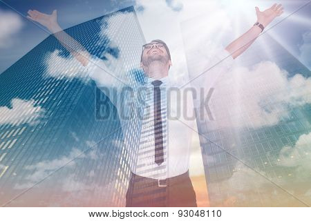 Cheering businessman with his arms raised up against low angle view of skyscrapers at sunset