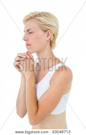 Pretty blonde woman praying on white background