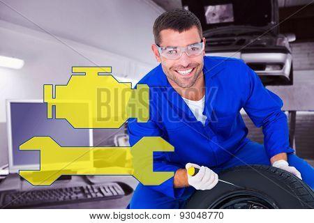 Portrait of happy mechanic working on tire against auto repair shop