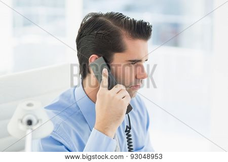 Thoughtful businessman having phone call in his office