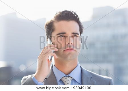 Thoughtful businessman calling on the phone at the patio