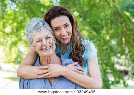 mother and grandmother smilling in a park on a sunny day