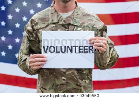 American soldier holding recruitment sign against american flag