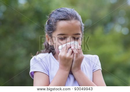 Little girl blowing his nose on a sunny day