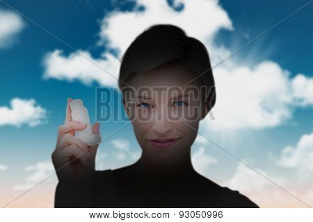 Pretty woman holding inhaler smiling at camera against blue sky