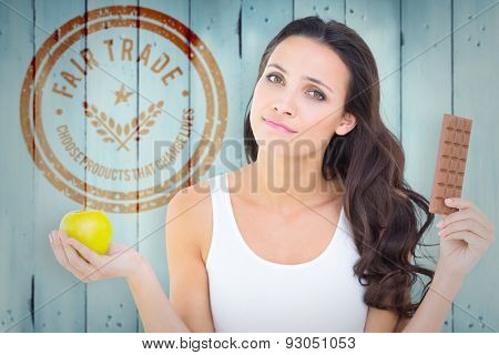 Pretty brunette deciding between apple and chocolate against wooden planks