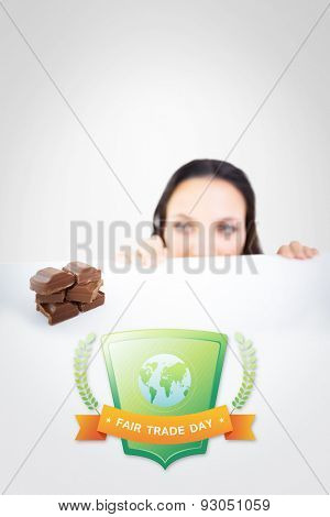 Pretty brunette peeking at chocolate against grey vignette
