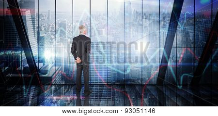 Businessman standing against stocks and shares on black background