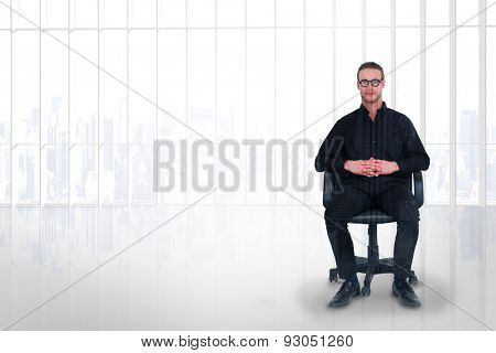 Stern businessman sitting on an office chair against room with large window looking on city