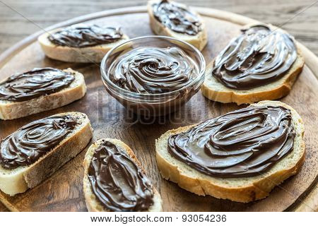 Slices Of Baguette With Chocolate Cream On The Wooden Board