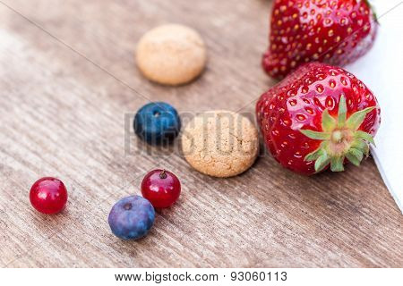 Some Berries And Amarettini Biscuits With Napkin On Wooden Board