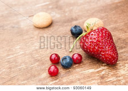 Some Berries And Amarettini Biscuits On Wooden Board
