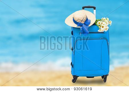 Travel bag with a straw hat and a bouquet of daisies on abstract sea background
