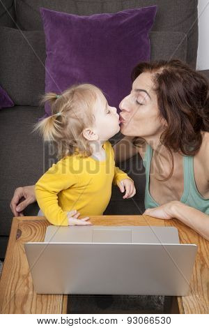 Baby And Mom Kissing With Laptop