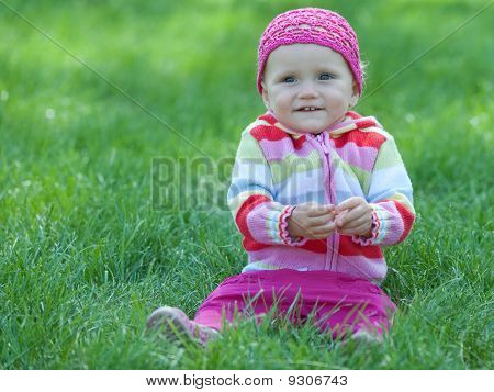 Kid In Pink Sitting On The Green Meadow