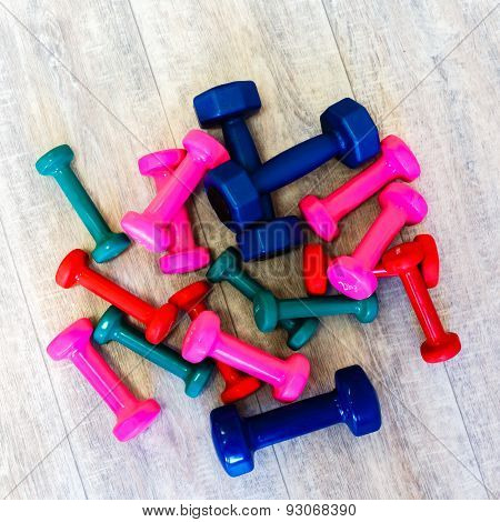 Group Of Colored Dumbbells On The Floor In The Gym