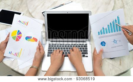 Business woman hand typing on laptop keyboard with Financial charts on the table