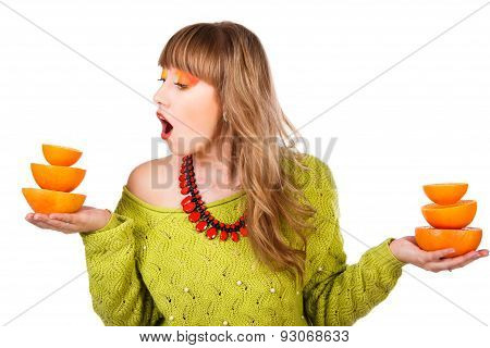 Cute Young Woman In A Green Sweater With Two Pyramids Of Orange Fruits