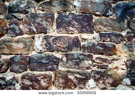 Background texture of a natural rock wall with roughly hewn rectangular bricks with rough weathered surfaces, full frame