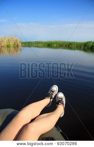 Feet Girl In Sneakers On The River Landscape