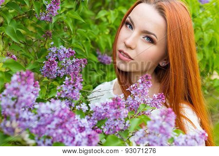 beautiful cute sexy red-haired girl with long hair in a white dress with a bouquet of lilac in